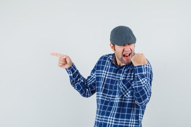 젊은 남자 셔츠, 모자 측면을 가리키고 운이 좋은, 전면보기를 찾고.