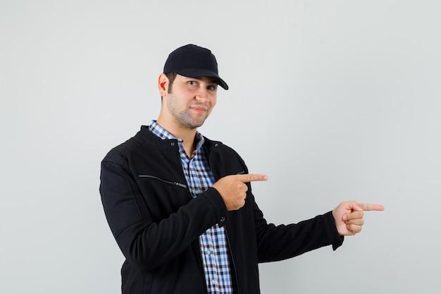Молодой человек, указывая в сторону в рубашке, куртке, кепке и выглядит весело, вид спереди.