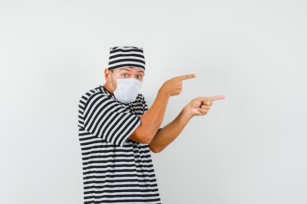 스트라이프 티셔츠 모자 마스크 측면을 가리키고 호기심을 찾는 젊은 남자