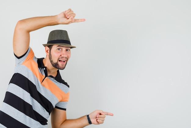 Tシャツ、帽子、嬉しそうに横を指している若い男。