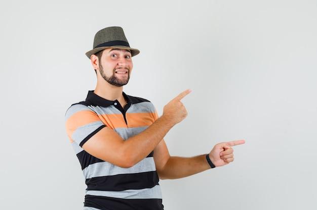 Tシャツ、帽子、楽観的に見える側を指している若い男。