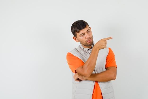 Tシャツ、ジャケットで横を指して、賢明に見える若い男。