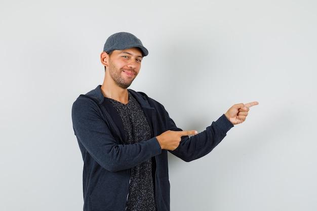 若い男は、tシャツ、ジャケット、キャップで横を指して、楽観的に見えます。