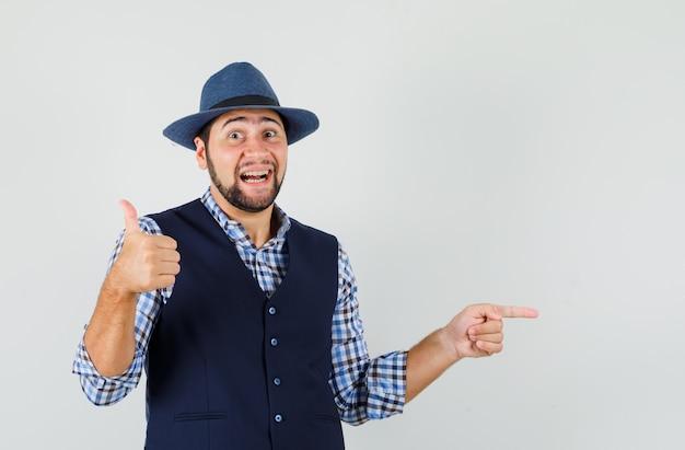 若い男が横を指して、シャツ、ベスト、帽子に親指を立てて、嬉しそうに見える