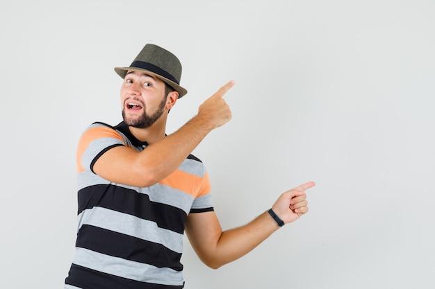 Tシャツ、帽子、陽気な顔で指を上に向けて横を指している若い男。