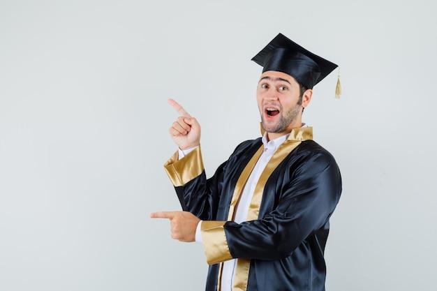 Молодой человек указывая вверх и в сторону в форме выпускника и глядя рад, вид спереди.
