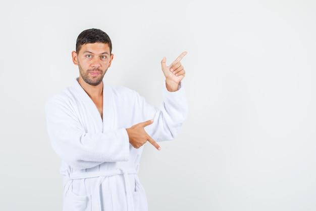 Молодой человек указывая вверх и вниз с жестом пистолета в белом халате вид спереди.