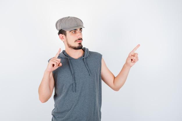 회색 티셔츠와 모자에 검지 손가락으로 위쪽 및 오른쪽을 가리키고 심각한 찾고 젊은 남자