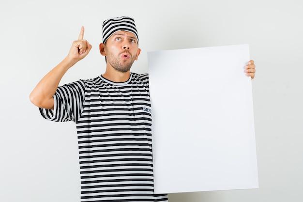 Молодой человек указывая вверх, держа чистый холст в полосатой футболке, шляпе и с любопытством глядя.