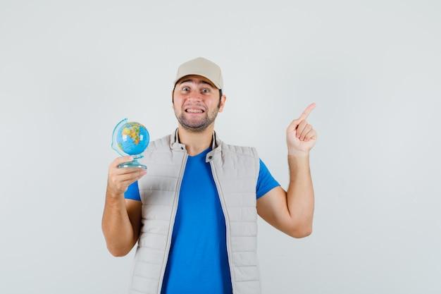 若い男が上向き、tシャツ、ジャケット、キャップで学校の地球儀を保持し、嬉しそうに見える、正面図。