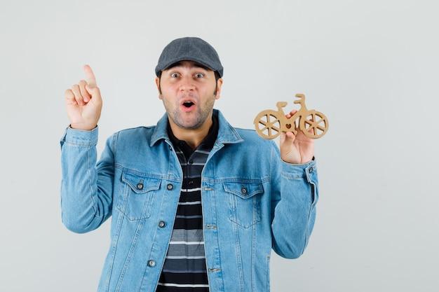 若い男が上を向いて、tシャツ、ジャケット、キャップで木のおもちゃの自転車を持って、驚いて見える、正面図。