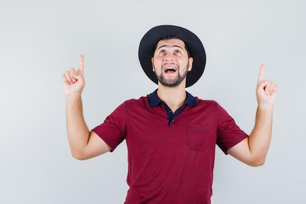 若い男が赤いtシャツで上向き、帽子と驚いて見える、正面図。