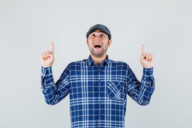 若い男はシャツ、キャップを指して、感謝しているように見えます。正面図。