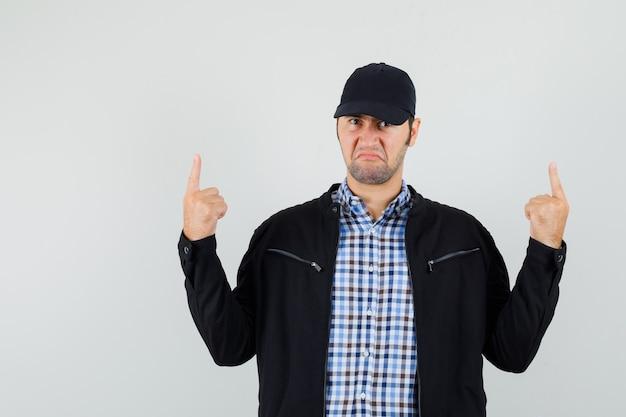 Молодой человек указывая вверх в рубашке, куртке, кепке и недоволен, вид спереди.