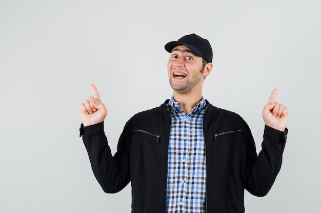 Молодой человек, указывая вверх в рубашке, куртке, кепке и глядя с надеждой, вид спереди.