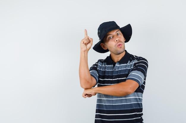 Молодой человек, указывая вверх в футболке, шляпе и глядя внимательно, вид спереди.