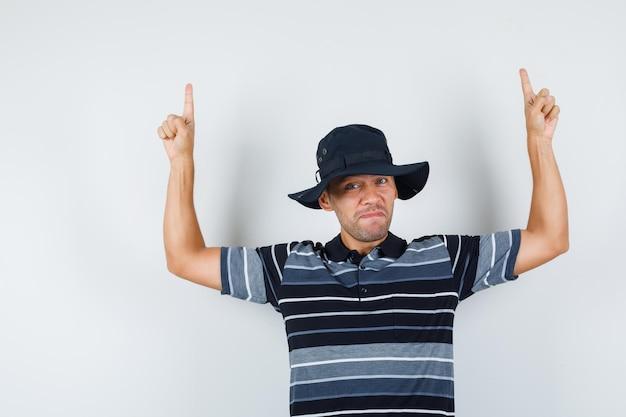 Молодой человек указывая вверх в футболке, шляпе и выглядит уверенно, вид спереди.