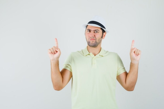 若い男はtシャツ、帽子を指して、疑わしい顔をしています。