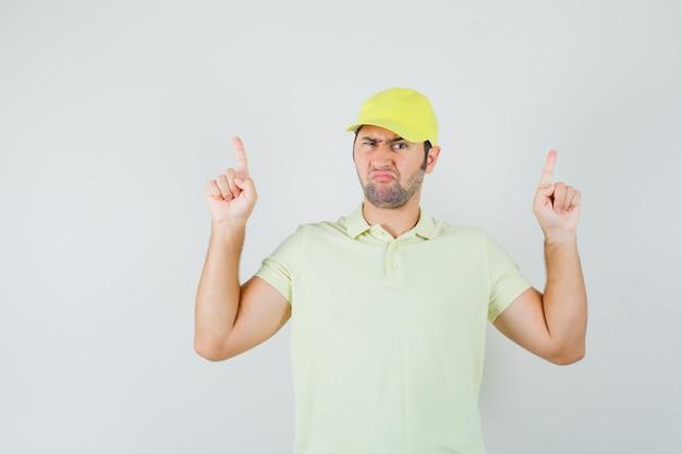 노란색 유니폼을 가리키고 주저 찾고 젊은 남자.