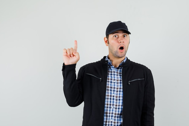 Young man pointing up in shirt, jacket, cap and looking surprised , front view.