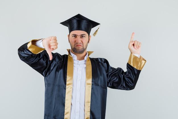 Молодой человек указывая вверх, показывая большой палец вниз в униформе выпускника и выглядел мрачно. передний план.