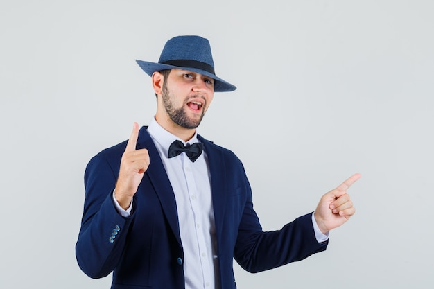 Young man pointing up and to the side in suit, hat and looking confident , front view.