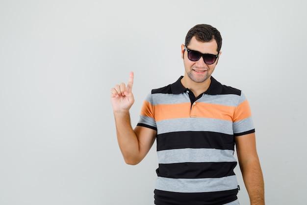 Giovane uomo rivolto verso l'alto in t-shirt, occhiali da sole e guardando fiducioso. vista frontale.