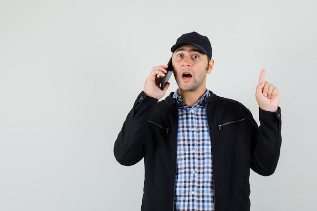 Молодой человек указывая вверх, разговаривает по мобильному телефону в рубашке, куртке, кепке и выглядит удивленным. передний план.