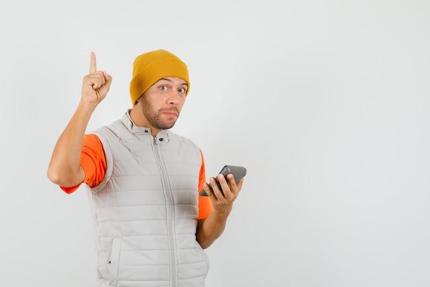T- 셔츠, 재킷, 모자에 계산기를 들고 가리키는 젊은 남자