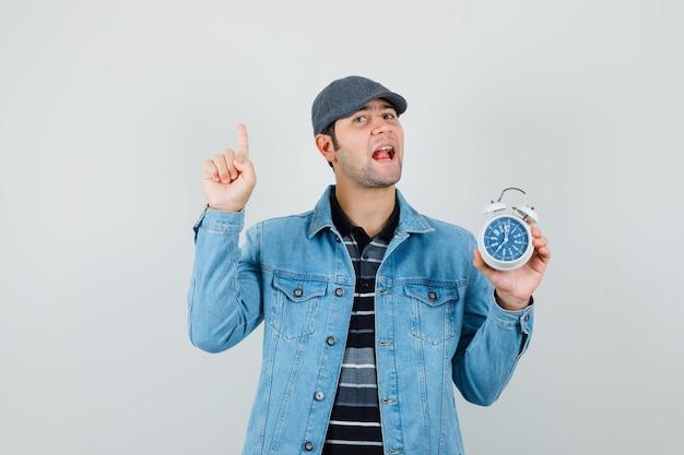 재킷, 모자에 시계를 들고 수다를 찾고있는 동안 가리키는 젊은 남자. 전면보기.