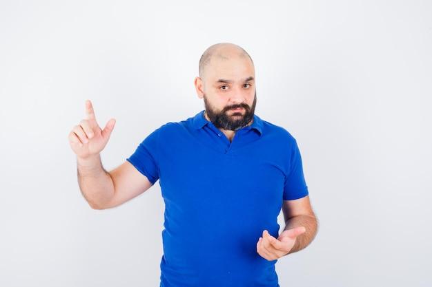 Giovane che indica in su mentre pensa in camicia blu e sembra concentrato. vista frontale.