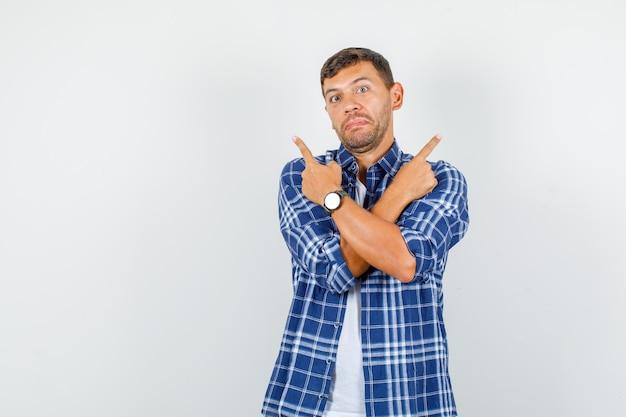 シャツを着て腕を組んで上を向いて混乱している若い男。正面図。
