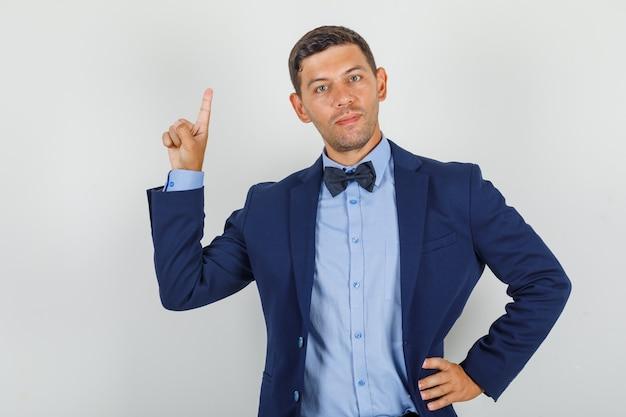 Молодой человек показывает рукой на талии в костюме и выглядит веселым