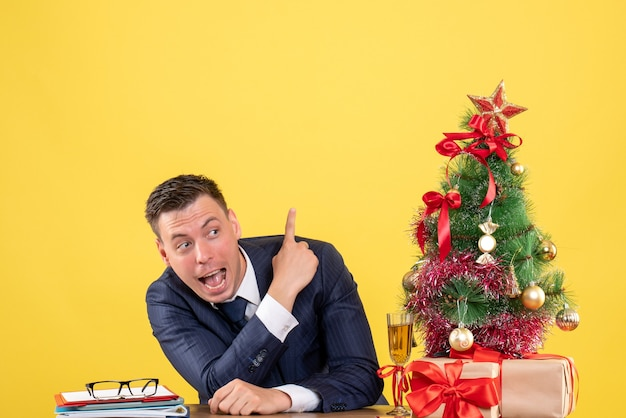 Young man pointing with finger. sitting at the table near xmas tree and presents on yellow