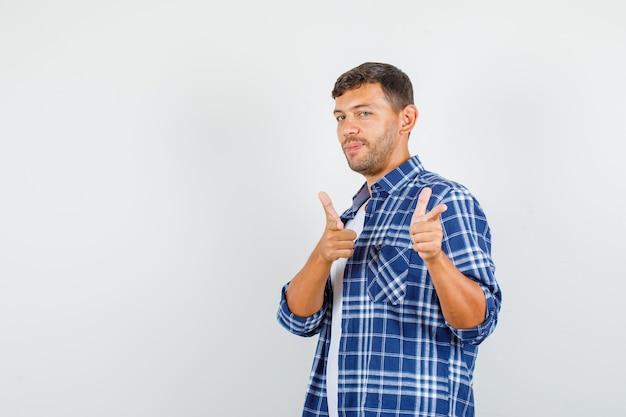 Молодой человек указывая жестом пистолета в рубашке и выглядит уверенно. передний план.