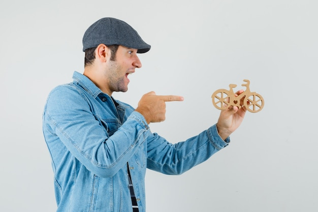 Young man pointing at wooden toy bike in cap, t-shirt, jacket and looking happy. .