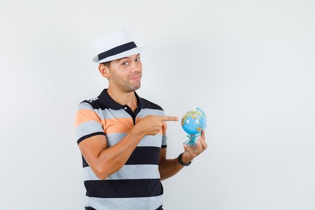 Giovane che indica al globo del mondo in maglietta e cappello e che sembra allegro