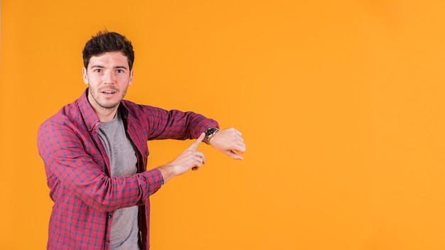 Young man pointing at wrist watch and looking at camera against orange background