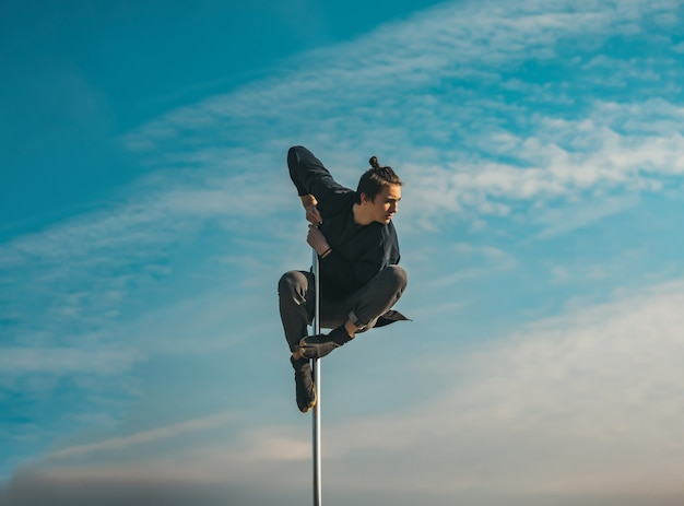 Young man pole dancing athletic man makes beautiful athletic acrobatic elements on a portable pylon on the blue sky surface