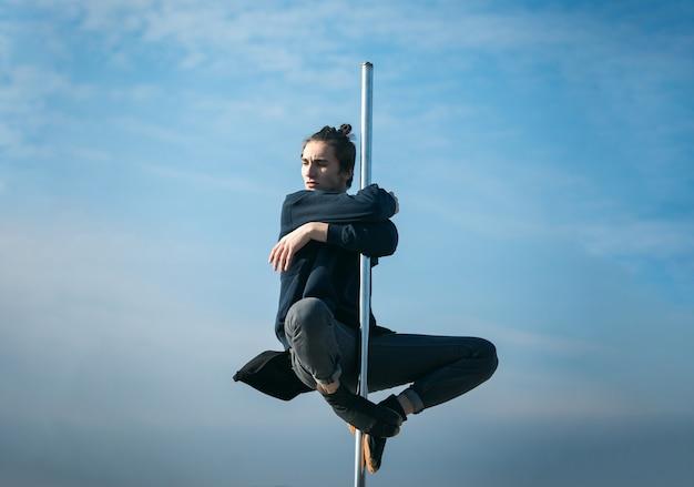 푸른 하늘 표면에 기둥에 앉아 젊은 남자 극 춤 섹시한 남자