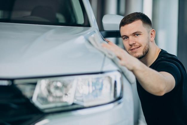 Молодой человек полирует свою машину тряпкой