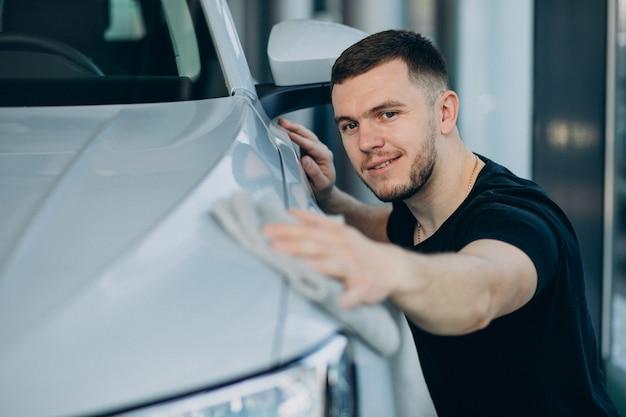 Young man polishing his car with rag