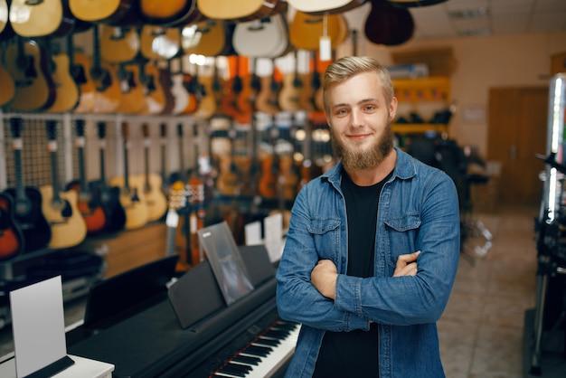 젊은 남자는 뮤직 스토어에서 쇼케이스에서 포즈. 악기 상점의 구색, 음악가 구매 장비, 시장의 음악 연주자