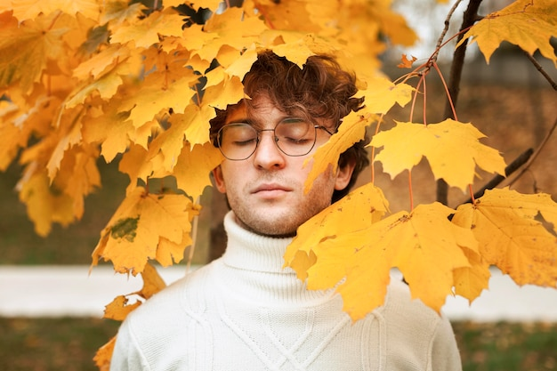 Giovane che propone in foglie di autunno