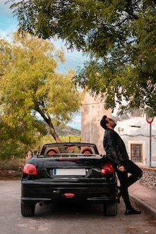 Young man posing in a convertible car.