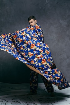 Young man posing in floral drape against grey wall