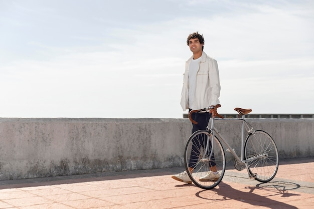 Young man posing next to his bike