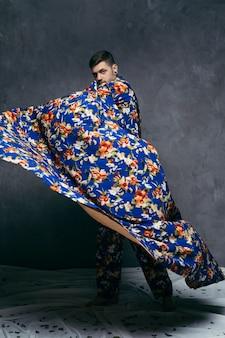 Молодой человек позирует в цветочной драпировке на серой стене