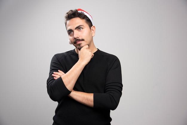 산타의 빨간 모자 생각에 포즈 젊은 남자.