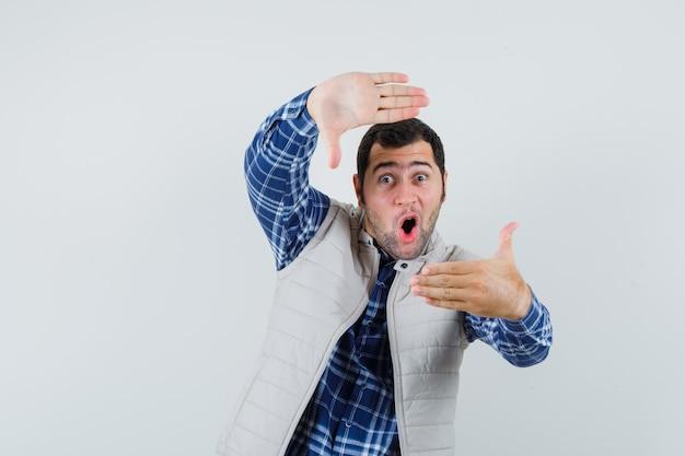 Молодой человек позирует, как фотографирующий в рубашке, куртке без рукавов и выглядит сосредоточенным, вид спереди.